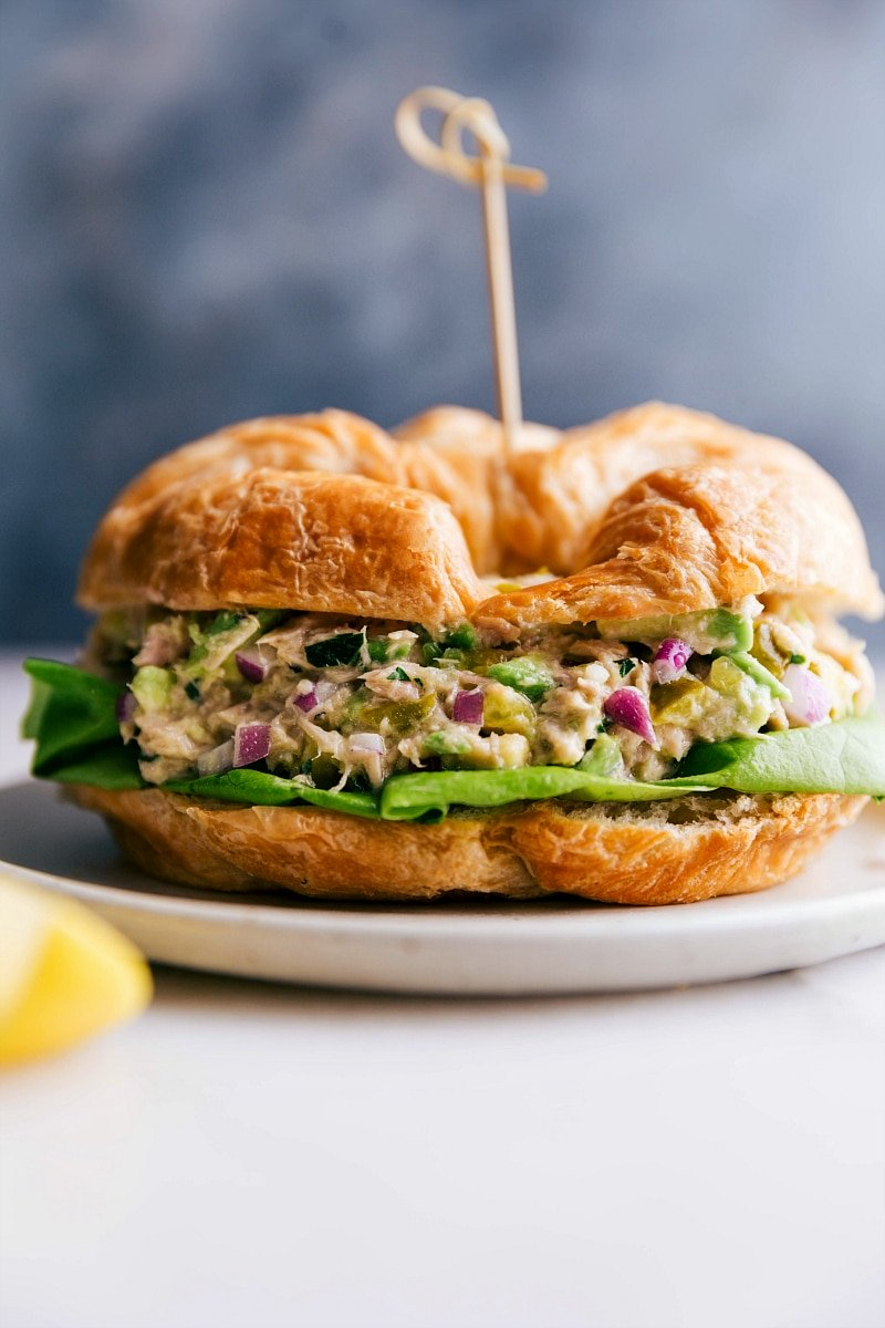 Up close image of Avocado Tuna Salad in a croissant ready to be eaten.