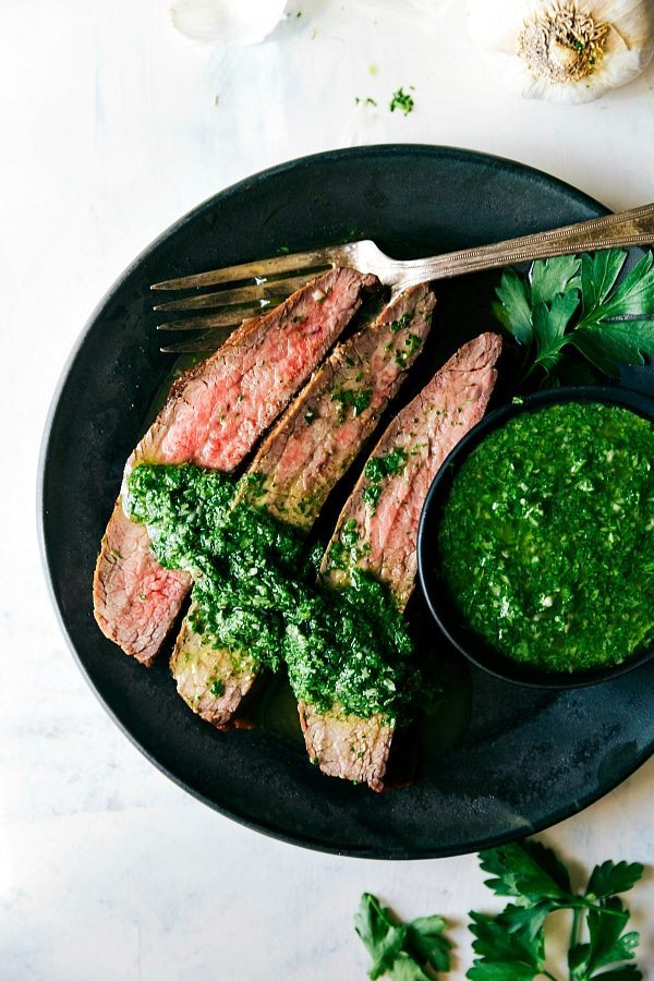 Easy grilled flank steak with a delicious marinade and an easy cilantro-parsley chimichurri. This grilled flank steak recipe includes a simple marinade, easy rub, and a delicious chimichurri sauce.