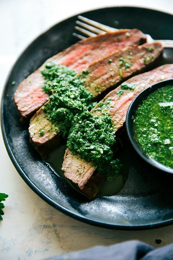 Easy grilled flank steak with a delicious marinade and an easy cilantro-parsley chimichurri. This grilled flank steak recipe includes a simple marinade, easy rub, and chimichurri sauce. Recipe via chelseasmessyapron.com