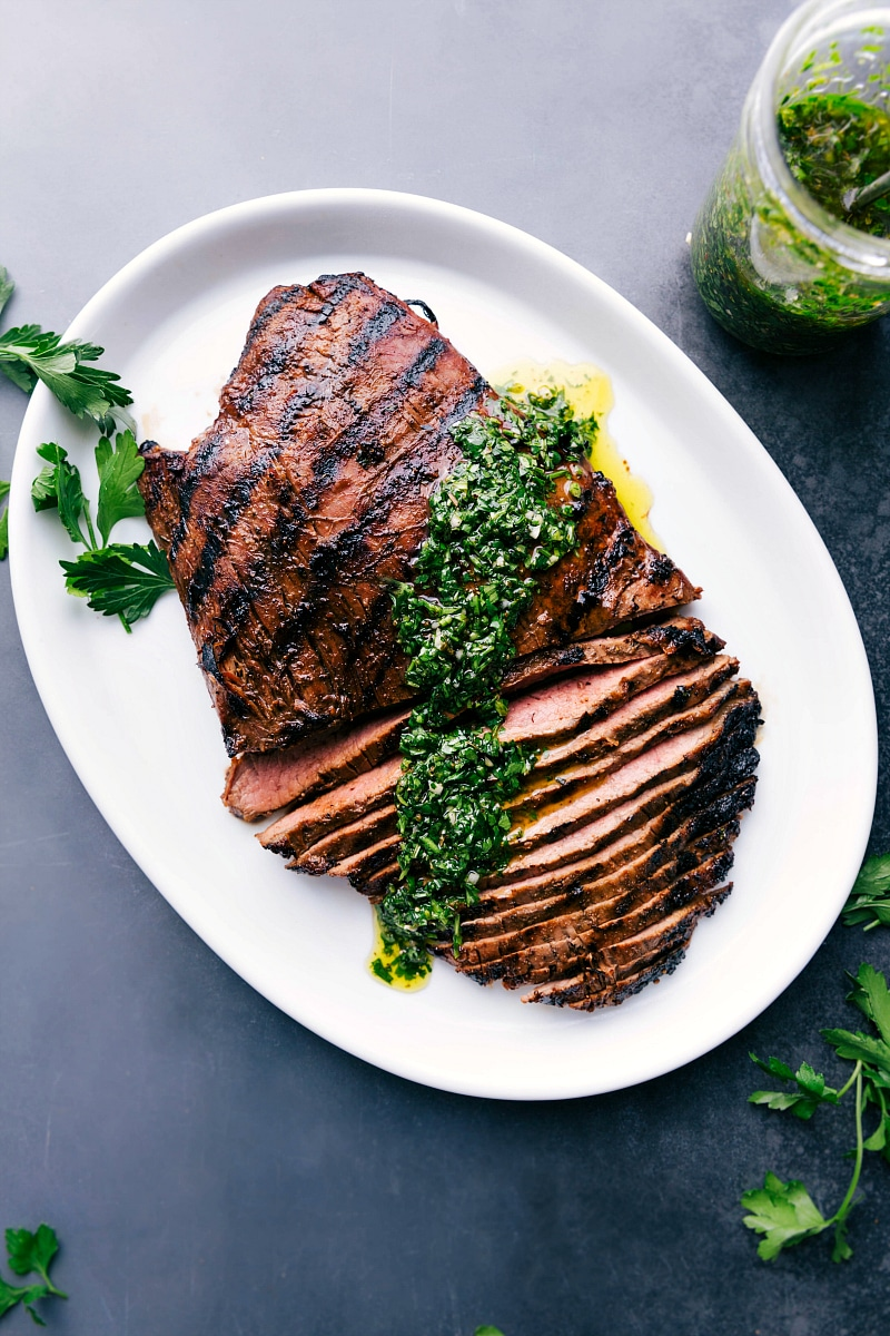 Overhead image of the grilled flank steak with chimichurri sauce over it