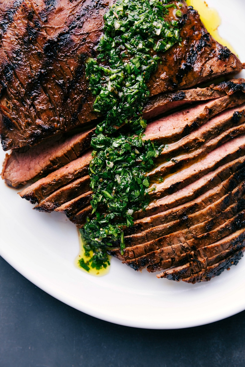 Overhead view of Grilled Flank Steak, sliced and topped with chimichurri sauce.