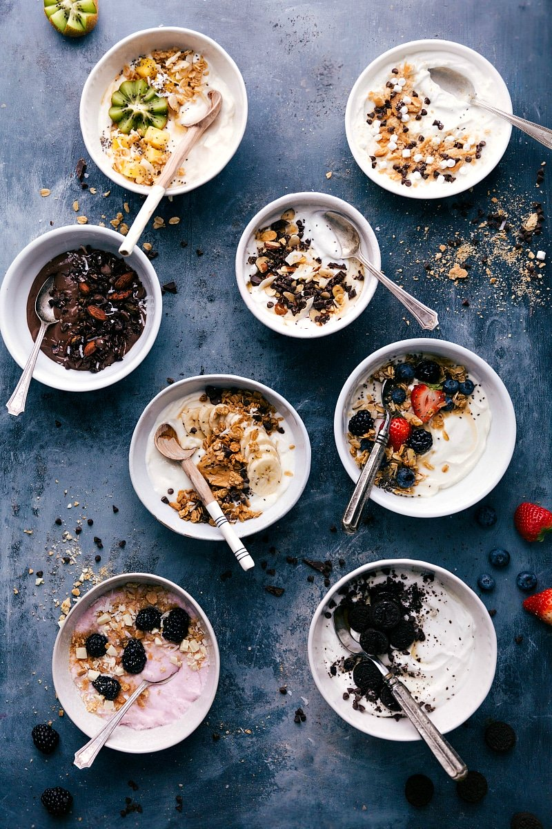 Overhead image of eight different yogurt bowls with spoons in them ready to be eaten.