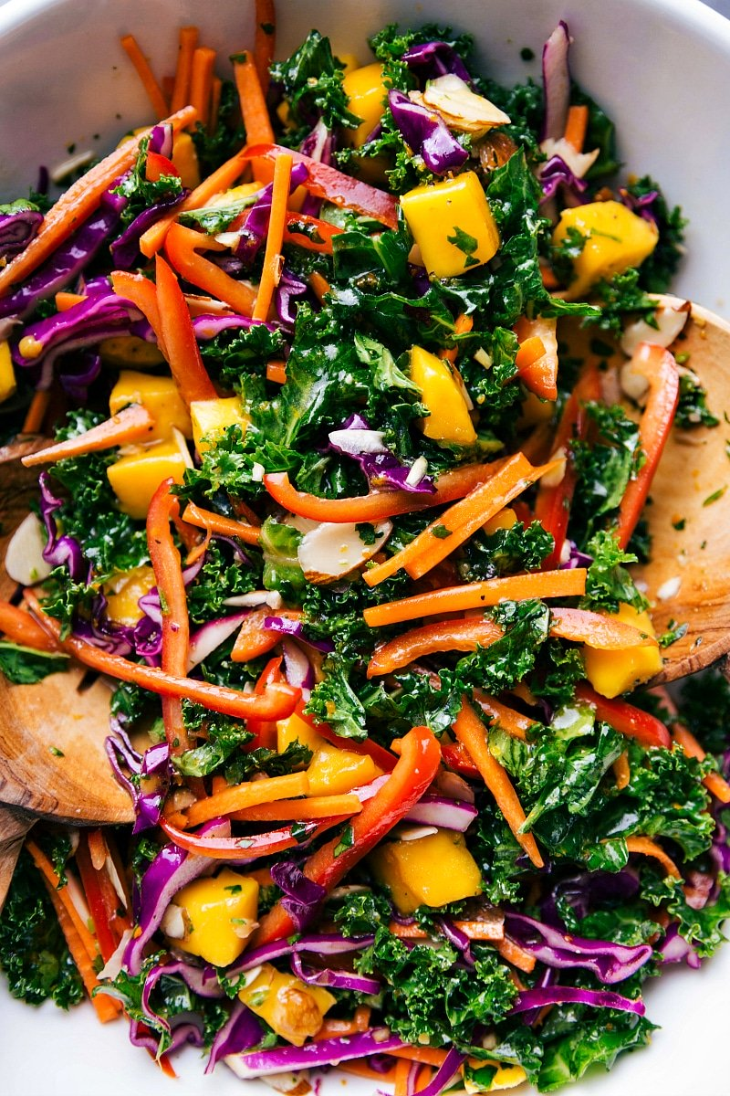 Overhead image of Kale Salad in a bowl, with wooden spoons in it.