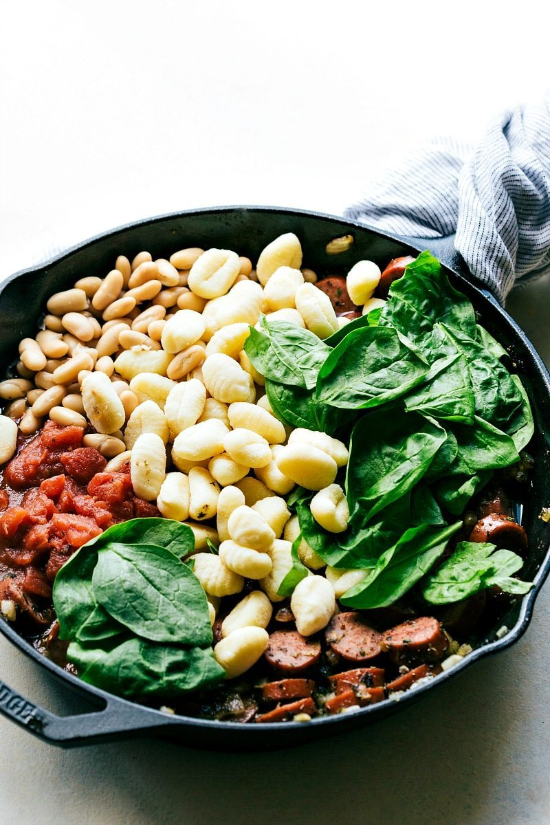 Only ONE skillet needed for a delicious 30 minute dinner recipe. Garlic, onion, sausage, white beans, gnocchi, tomatoes, and spinach