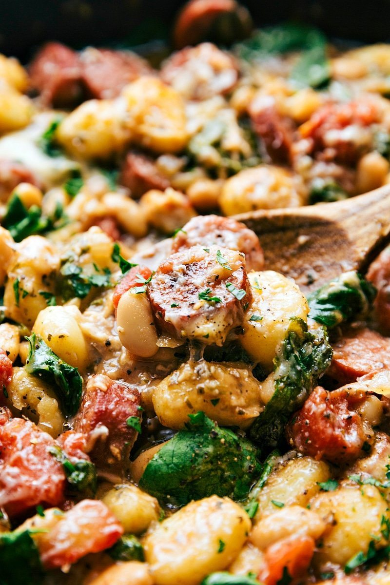 Only ONE skillet needed for a delicious 30 minute dinner recipe. Garlic, onion, sausage, white beans, gnocchi, tomatoes, and spinach via chelseasmessyapron.com