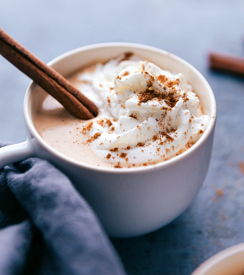 Up-close image of Pumpkin Spice Latte Steamer with whipped cream and a cinnamon stick.