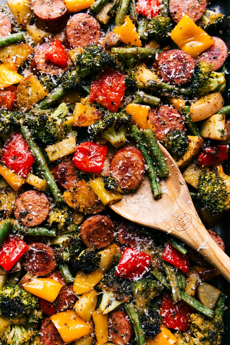 Overhead image of Sheet Pan Sausage and Veggies with a spoon, scooping some of it up.