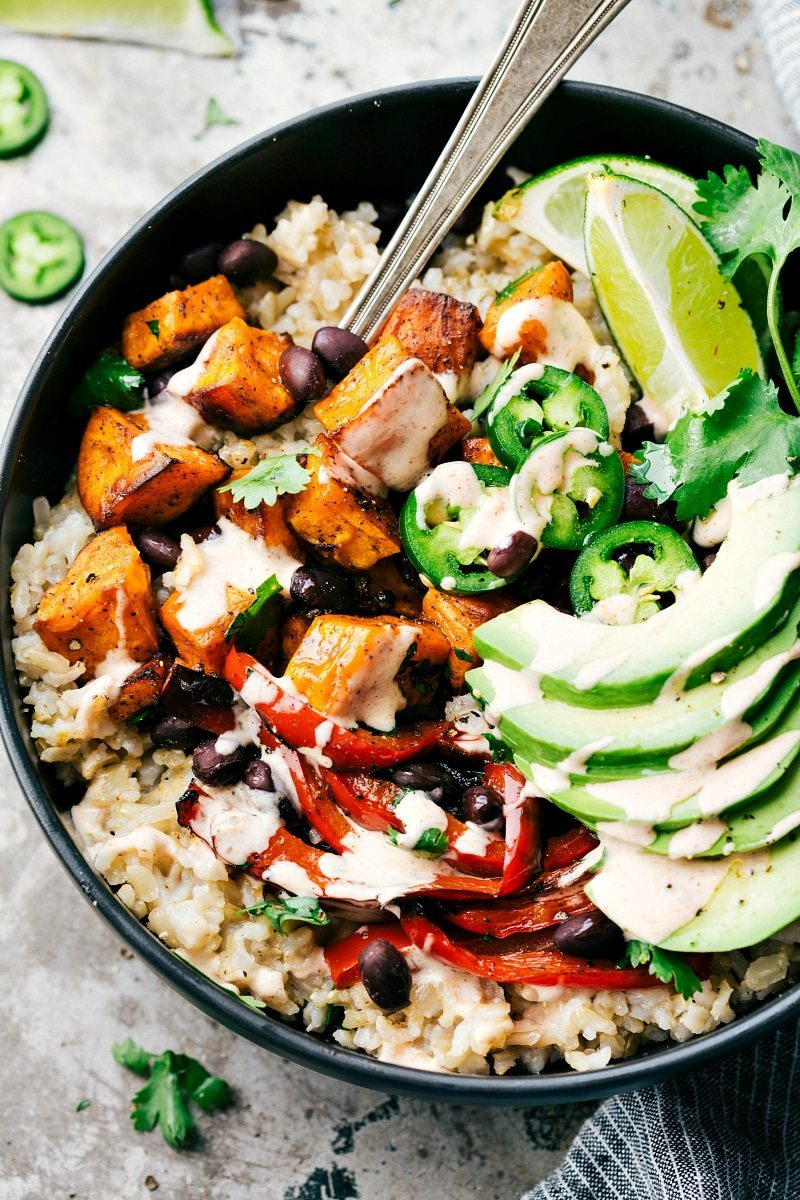 SWEET POTATO BURRITO BOWL! A delicious and simple to make veggie burrito bowl -- brown rice, seasoned & roasted sweet potatoes + bell peppers, black beans, and avocado with the most incredible chipotle lime sauce. Recipe via chelseasmessyapron.com