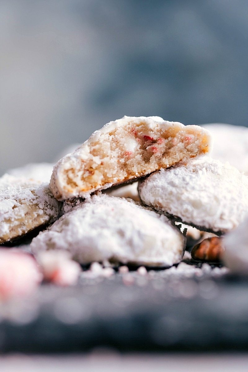Up-close image of Peppermint Snowball Cookies stacked on top of each other with a bite out of one of them.