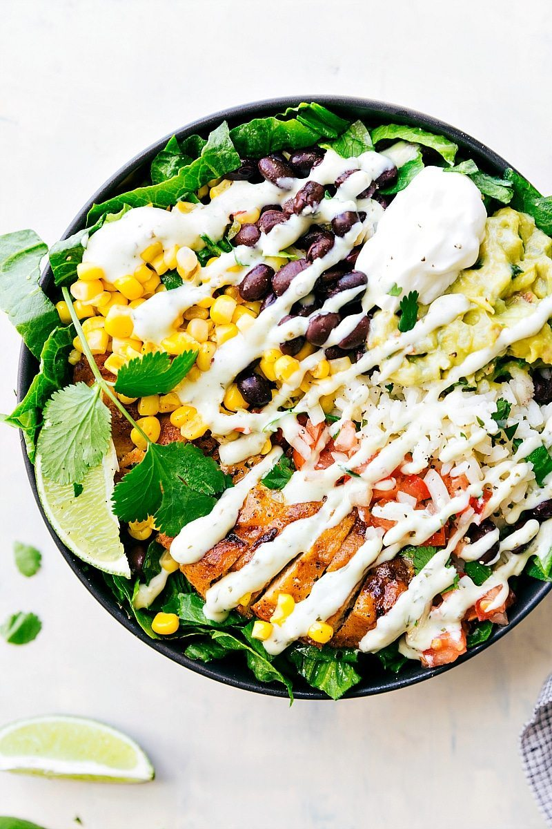 EASY MEAL PREP Chicken Burrito Bowls! Tons of short-cuts for a better than a restaurant burrito bowl! Taco-seasoned chicken, cilantro-lime rice, salsa, guac, beans, and a creamy cilantro sauce! Recipe from chelseasmessyapron.com