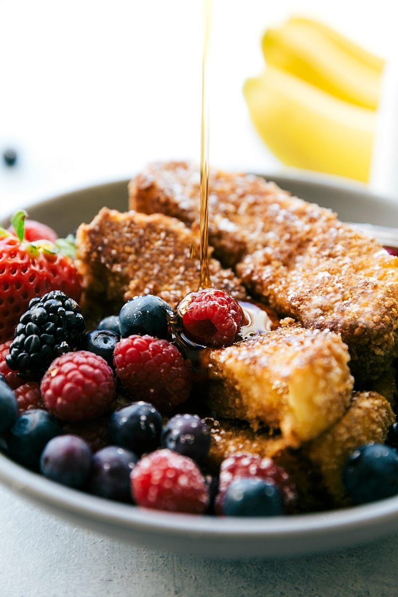 Image of the French toast sticks with syrup being poured over them and fruit on the side
