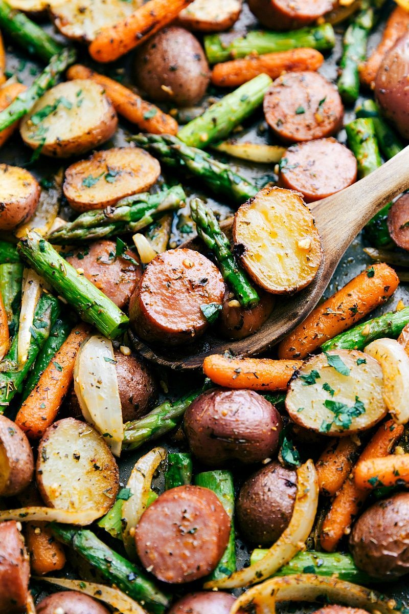 EASY ONE PAN ROASTED GARLIC POTATOES AND SAUSAGE! Red potatoes, asparagus, carrots, and sausage all with herbs. Recipe via chelseasmessyapron.com
