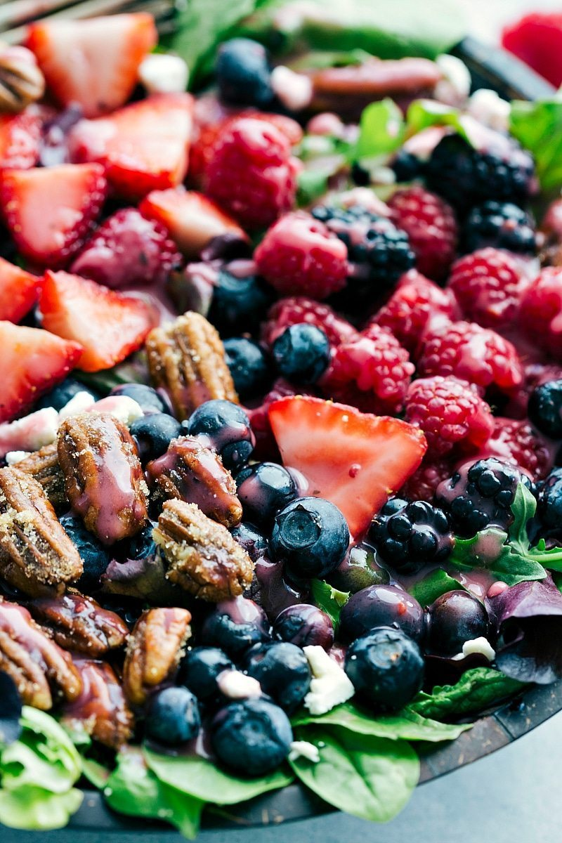The BEST berry salad with candied pecans and the ultimate raspberry vinaigrette! Recipe via chelseasmessyapron.com