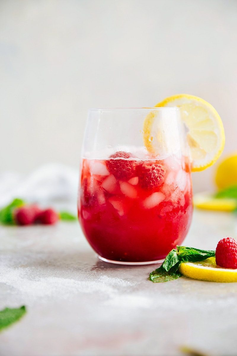 Image of the ready to drink raspberry lemonade with a lemon slice on the side and ice in it
