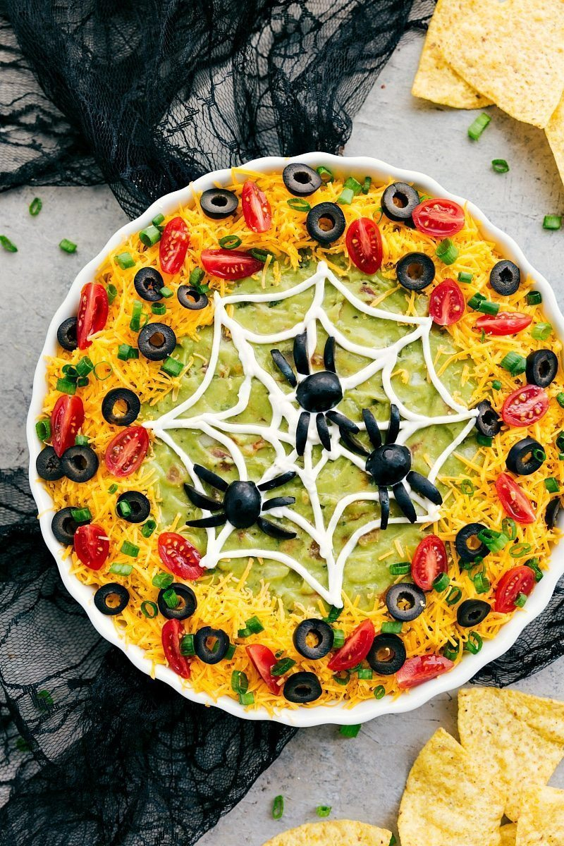 "Overhead photo of a 7 layer dip decorated to look like a spider web with olive ""spiders"" on top"