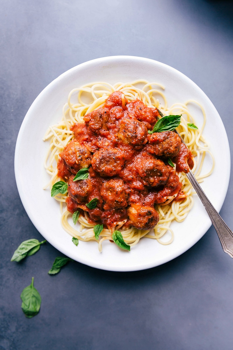 Overhead image of Chicken Parmesan Meatballs on a bed of pasta.