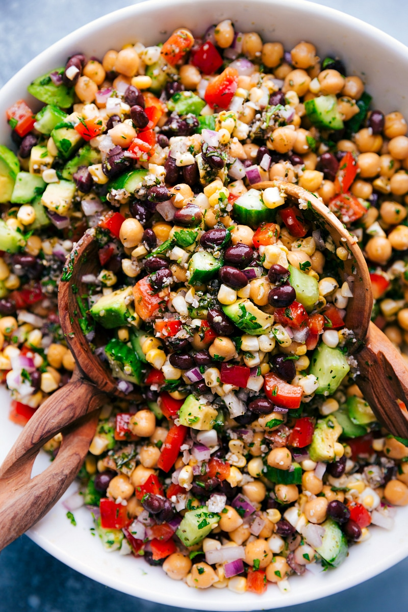 Overhead image of Garbanzo Bean Salad in a bowl with serving spoons