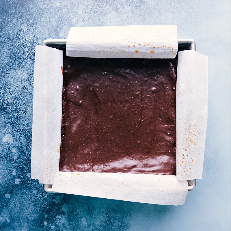 Healthy Brownies in the pan with a parchment paper overhang.