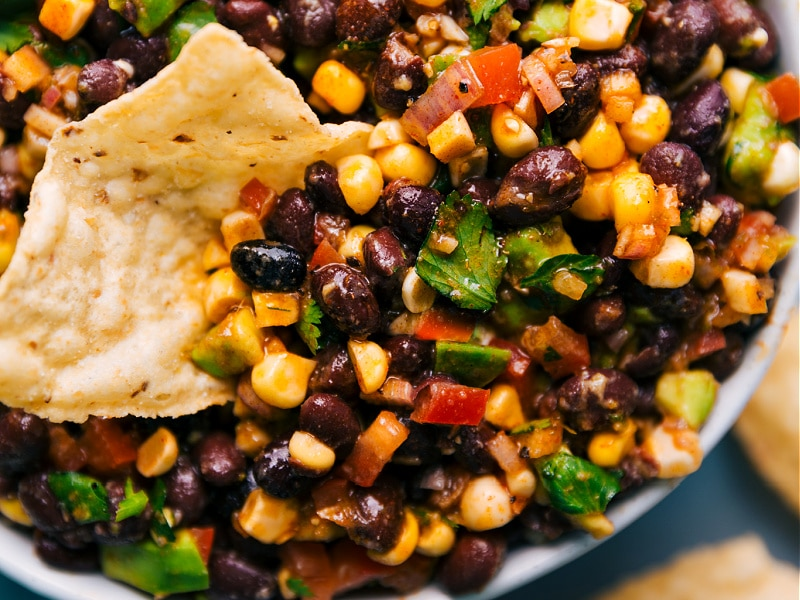 Image of the black bean corn avocado salad with a chip dipping into it
