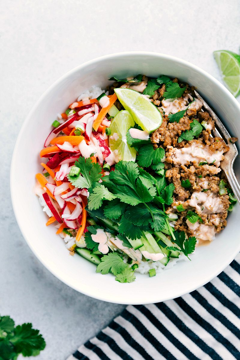 Picture of white bowl holding banh mi ingredients: rice, ground pork mixture, cilantro, cucumber, lime, pickled radish and carrot, and Sriracha mayo