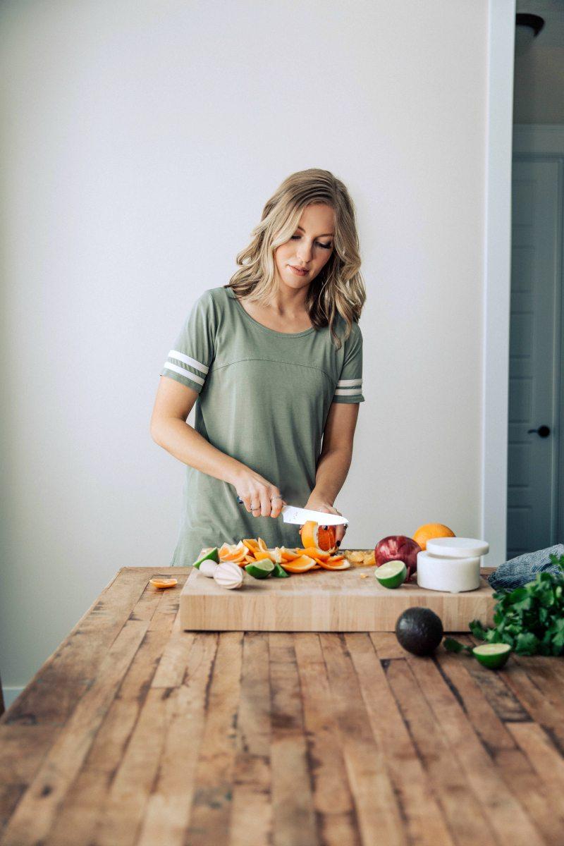 Author preparing citrus avocado salsa to top the healthy and easy grilled mojo chicken