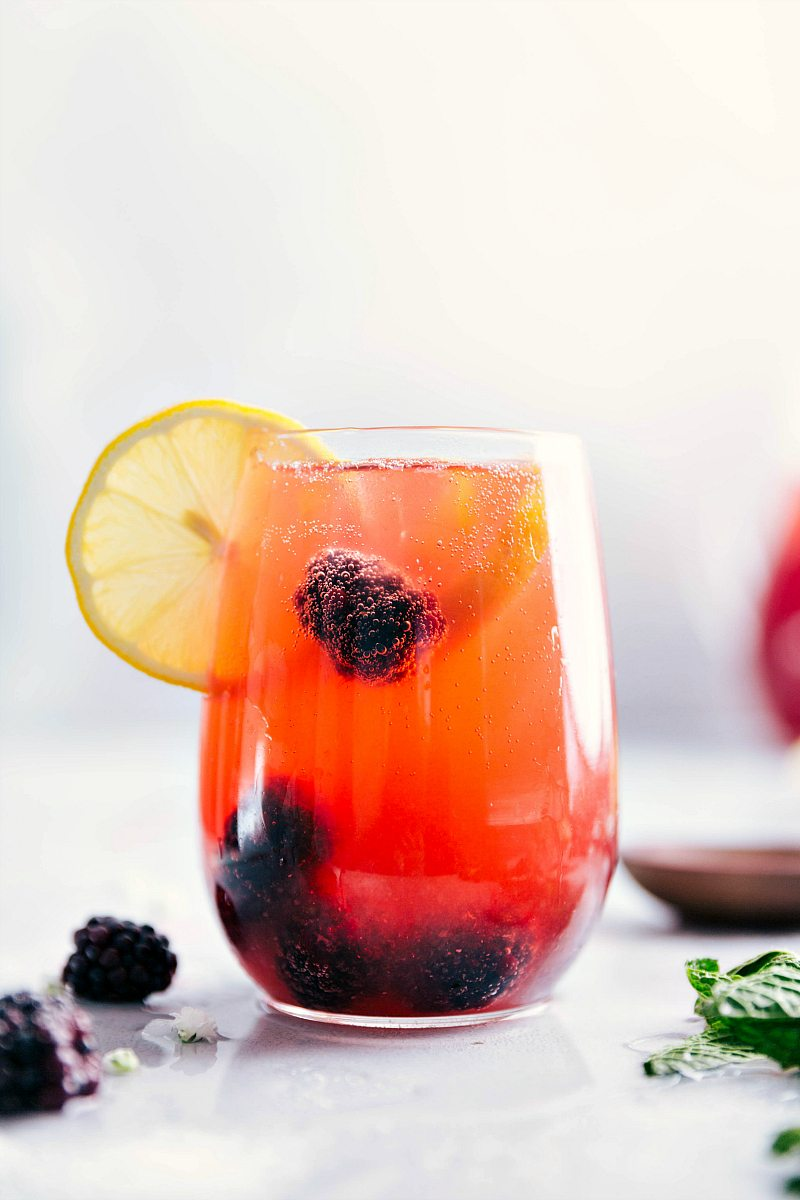 Up close shot of glass filled with sparkling blackberry lemonade and garnished with a slice of lemon