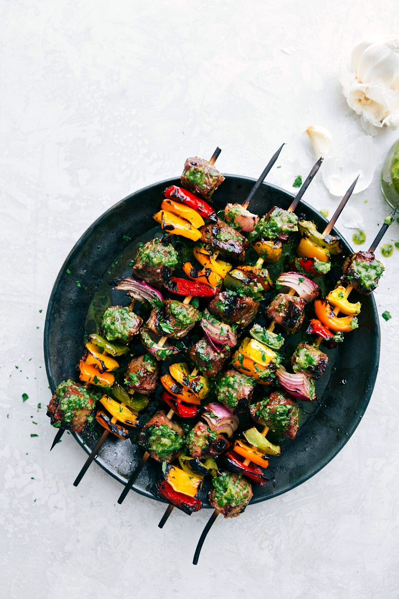Plate of steak kebabs with basil sauce on top