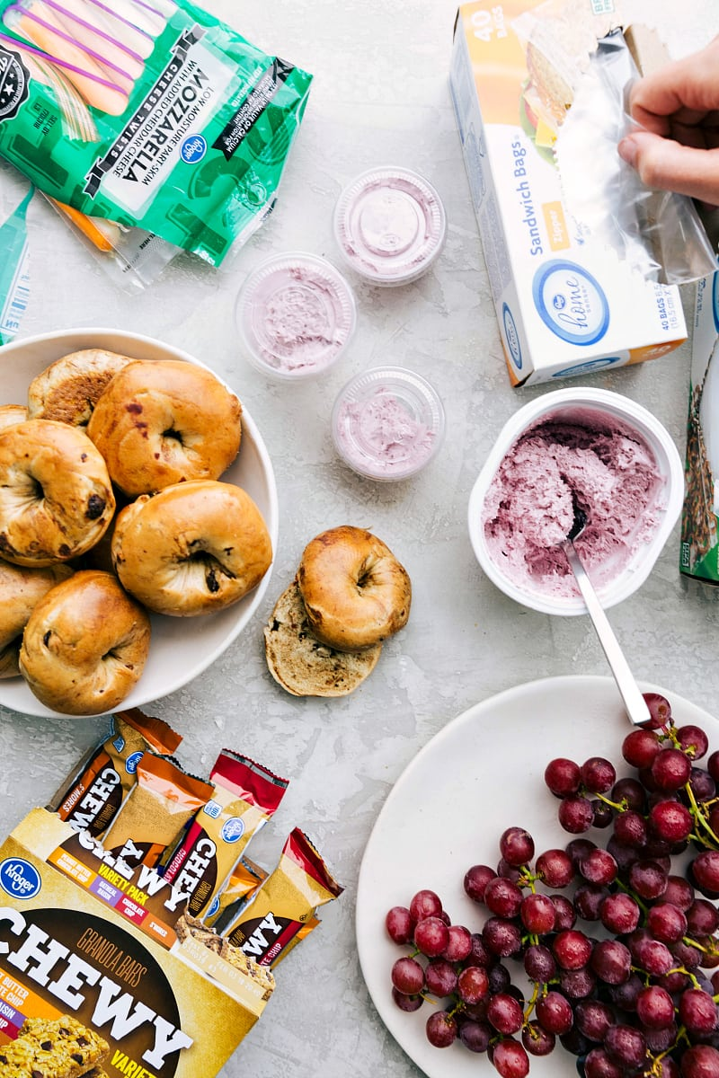 Overhead view of components of a healthy school lunch: bagels, string cheese, cream cheese, grapes and granola bars.
