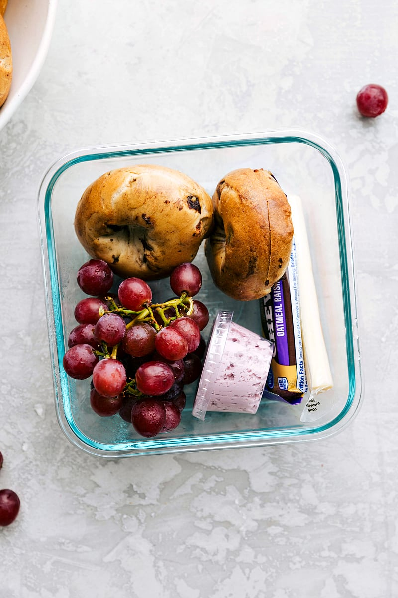 View of a baglel and fruit lunch for school.