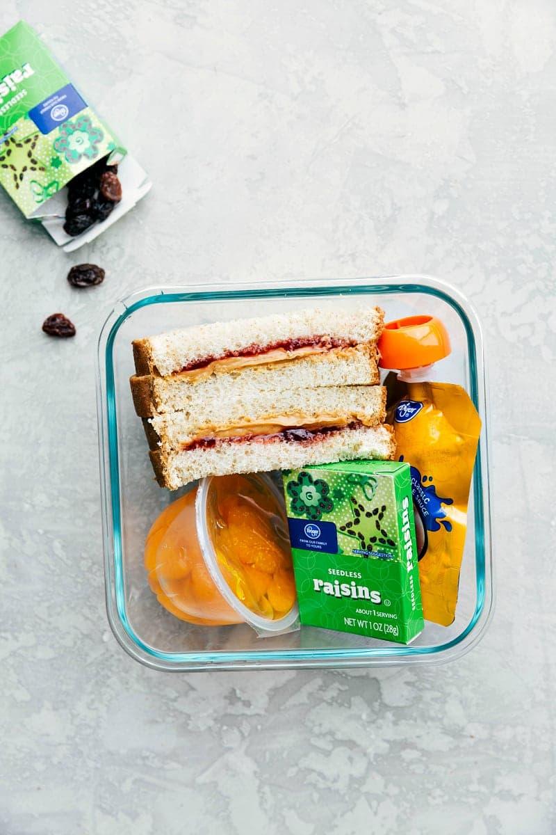 Overhead view of a school lunch: PBJ, raisins and Mandarin oranges.