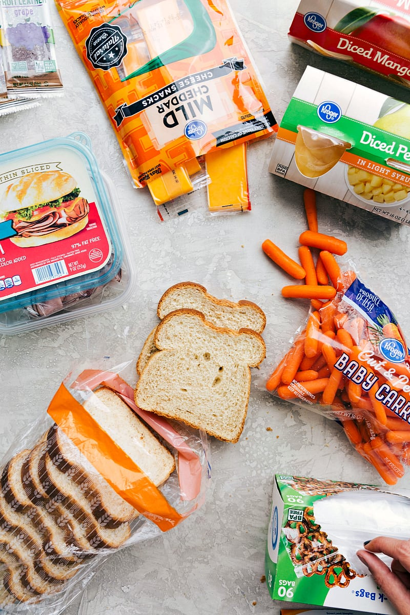 View of the components in another good school lunch: sliced deli meat, cheese, fruit, bread, veggies and a fruit snack.