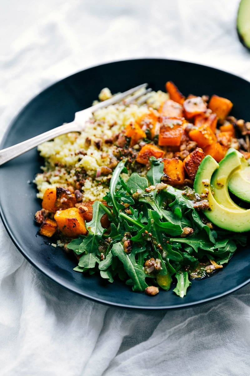 Side angle view of a plate with the perfect roasted butternut squash, couscous, and the best dressing! A perfect healthy Fall meal