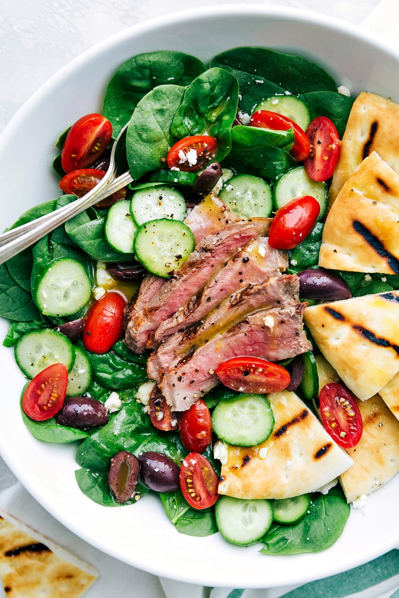 Grilled steak and pitas tossed with baby spinach, cucumbers, tomatoes, kalamata olives, and feta cheese dressed in a delicious lemon-honey vinaigrette. This steak salad is simple to make, healthy, and packed with flavor!