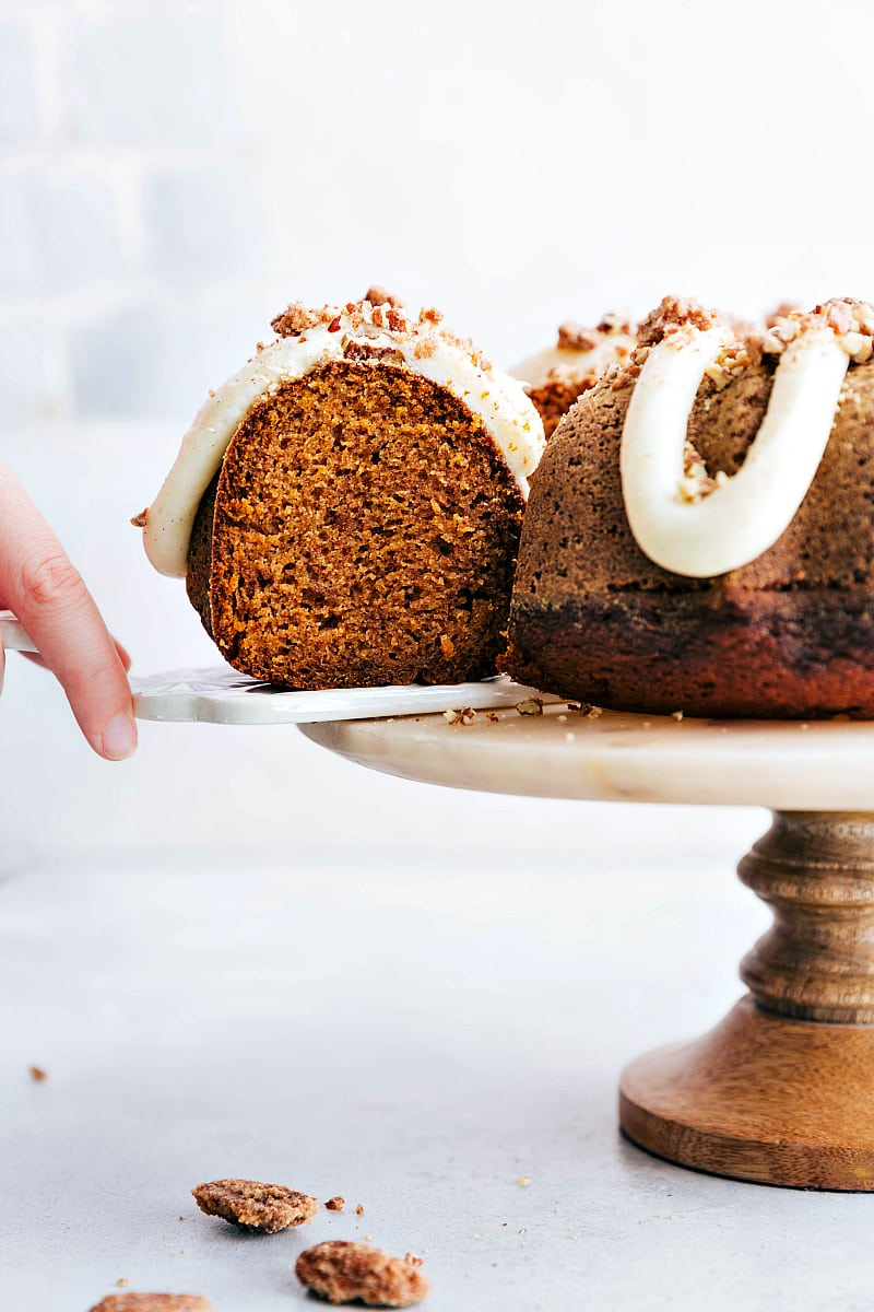 Hand is pulling a slice of pumpkin cake with cream cheese frosting from the rest of the cake that is resting on a cake stand.