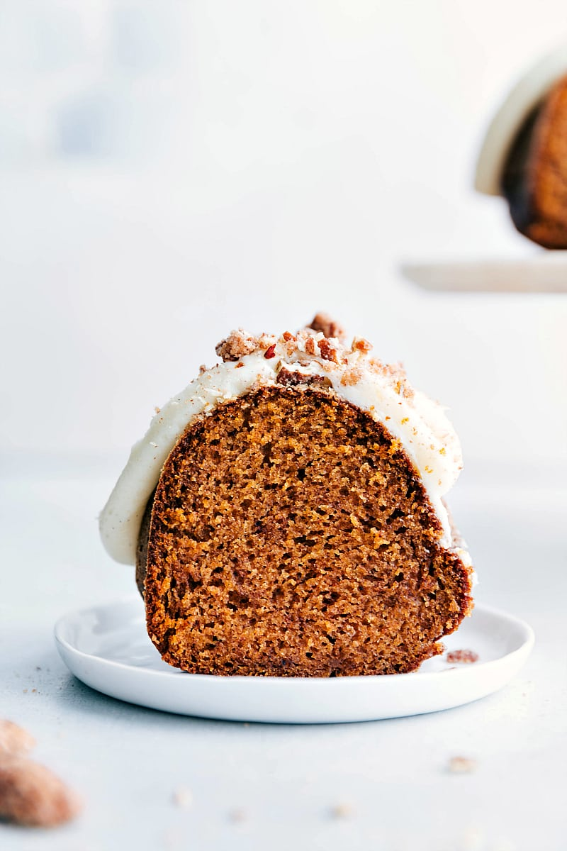 Up close shot of a slice of pumpkin cake with cream cheese frosting on a plate