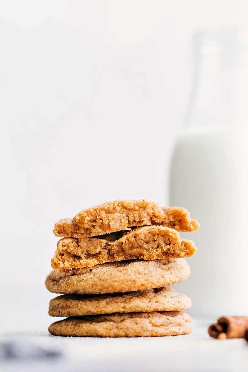 Up close photo of a stack of pumpkin snickerdoodle cookies. The top cookie is broken in half so you can see the soft and chewy interior