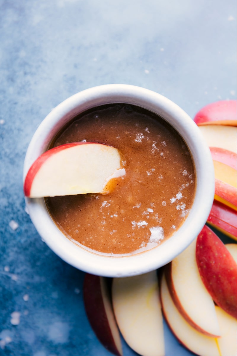 An apple slice dipped in Healthy Caramel Sauce