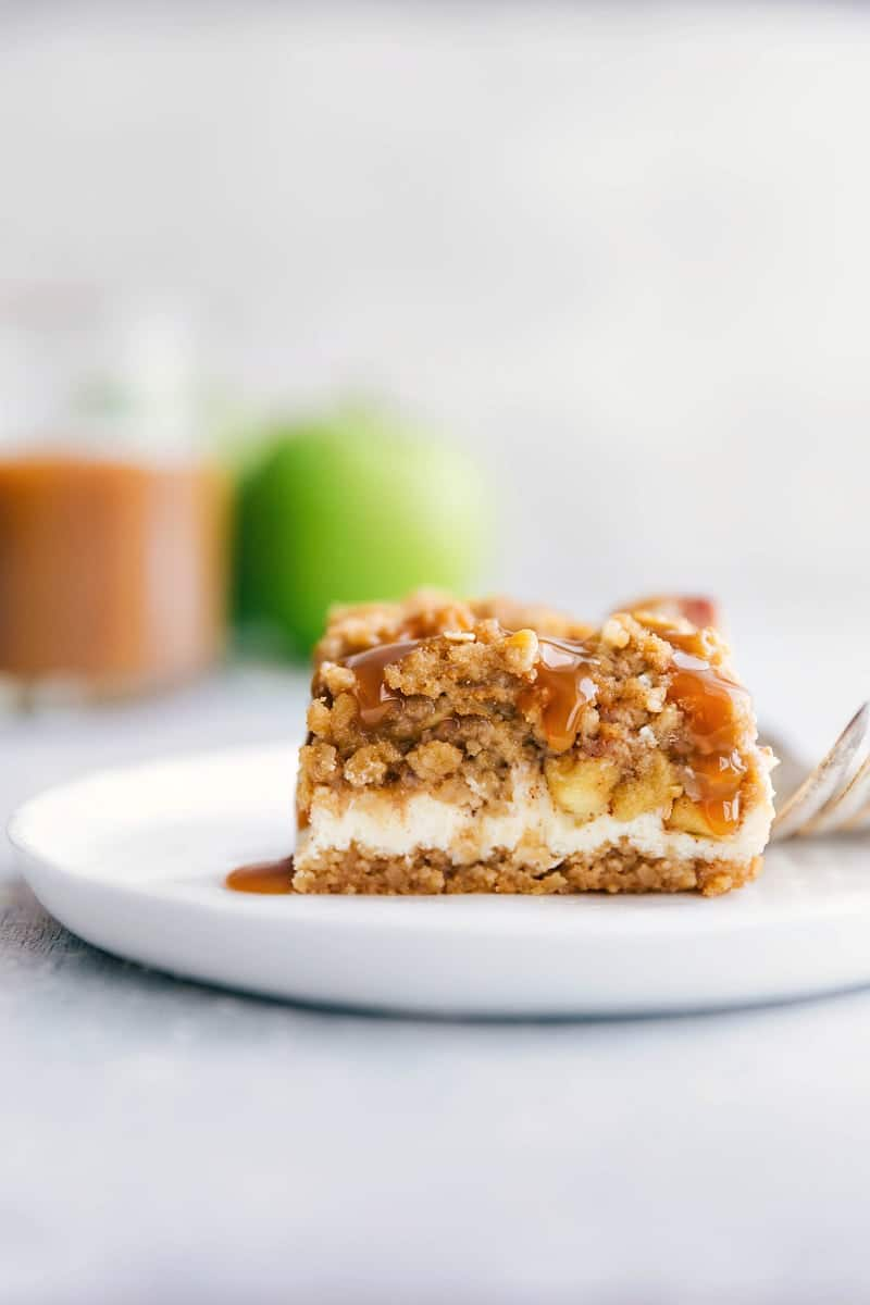 Up close photo of two caramel apple cheesecake bars stacked on top of each other with drippy caramel and apple in background