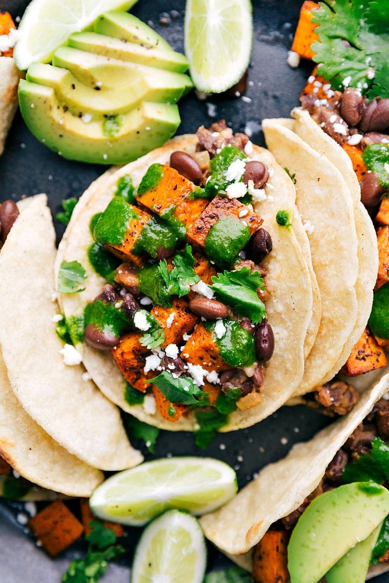 Overhead up-close shot of easy vegetarian tacos with garnishes and fresh cilantro lime dressing