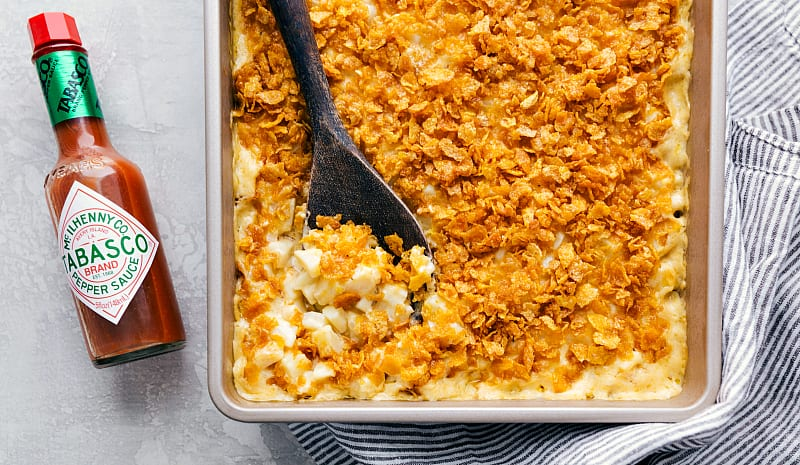 Finished funeral potatoes with a spoon digging in to serve