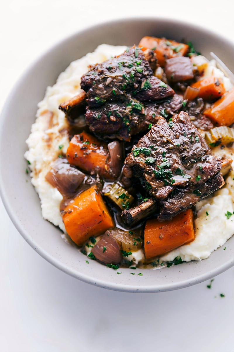 Up close photo of finished short ribs in a plate with mashed potatoes and vegetables