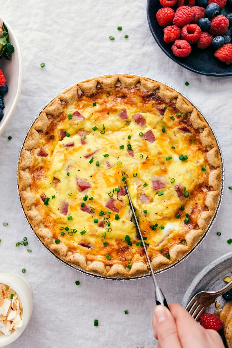 Overhead photo of a ham and cheese quiche being cut into