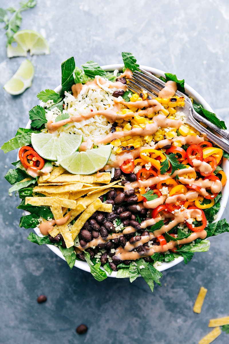 Overhead image of the ready to eat black bean and corn salad with the dressing over it and a fork on the side