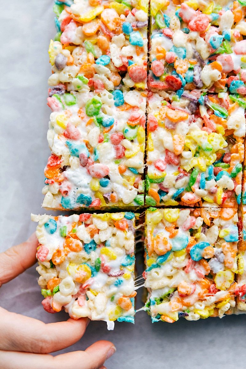 Child's hand pulling a Fruity Pebbles Rice Krispie Treat from all the other bars.