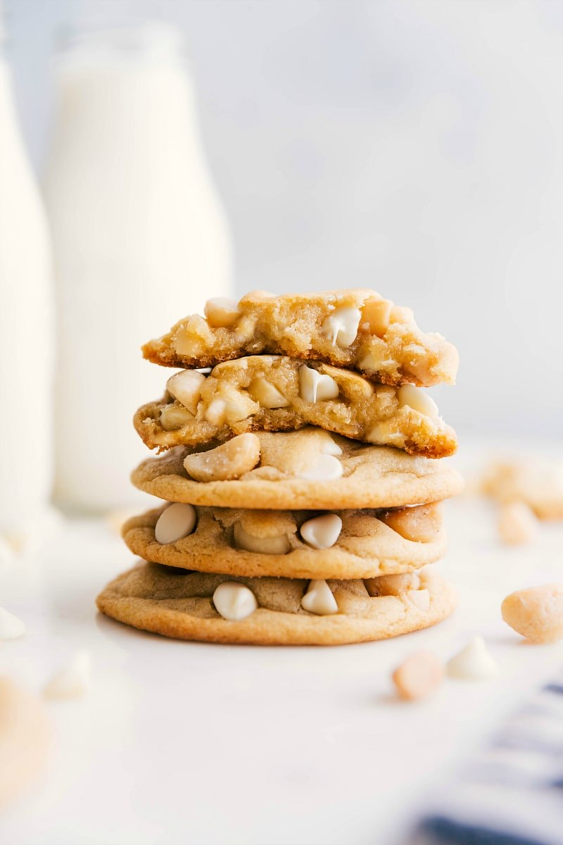 Image of ready-to-eat White Chocolate Macadamia Nut Cookies stacked with one broken in half.