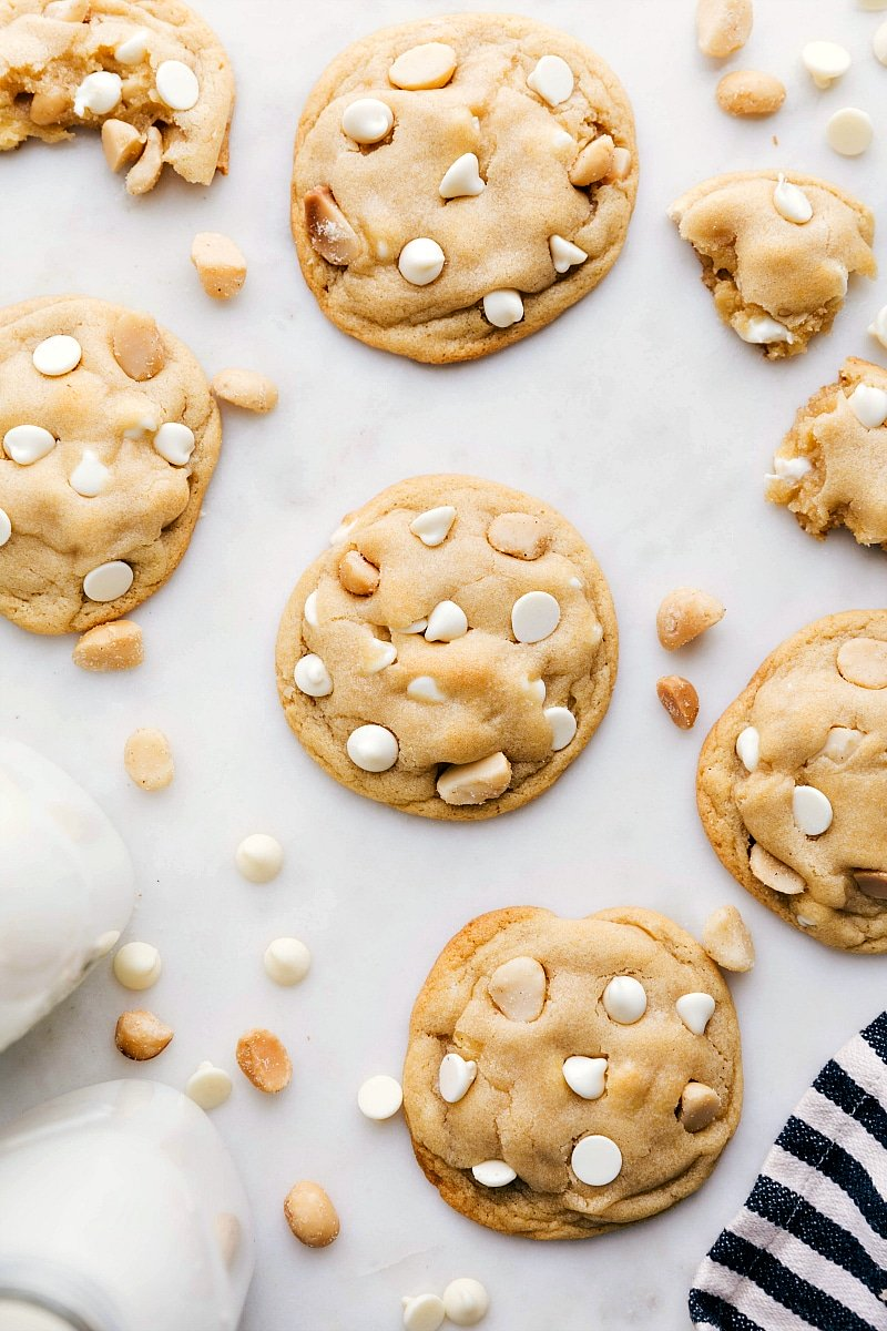 Image of the baked white chocolate macadamia nut cookies on a board with milk