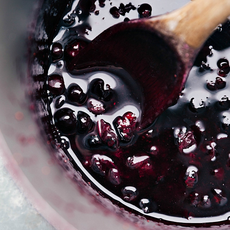 Up close image of the blueberry syrup on a wooden spoon in the saucepan