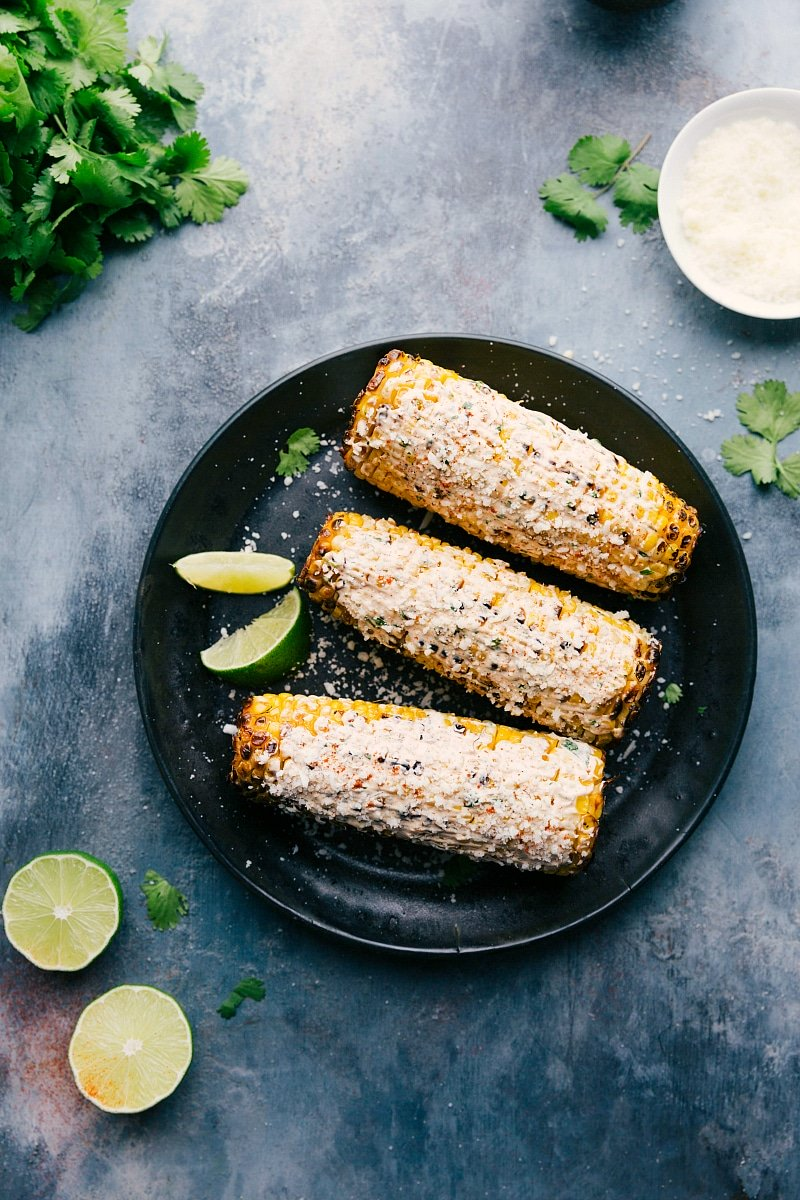 Image of the ready to eat Elotes on a plate with limes and cilantro around it