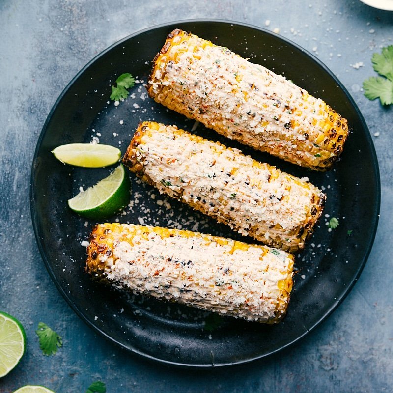 Image of the ready to eat Elote corn recipe on a plate with lime wedges and cilantro