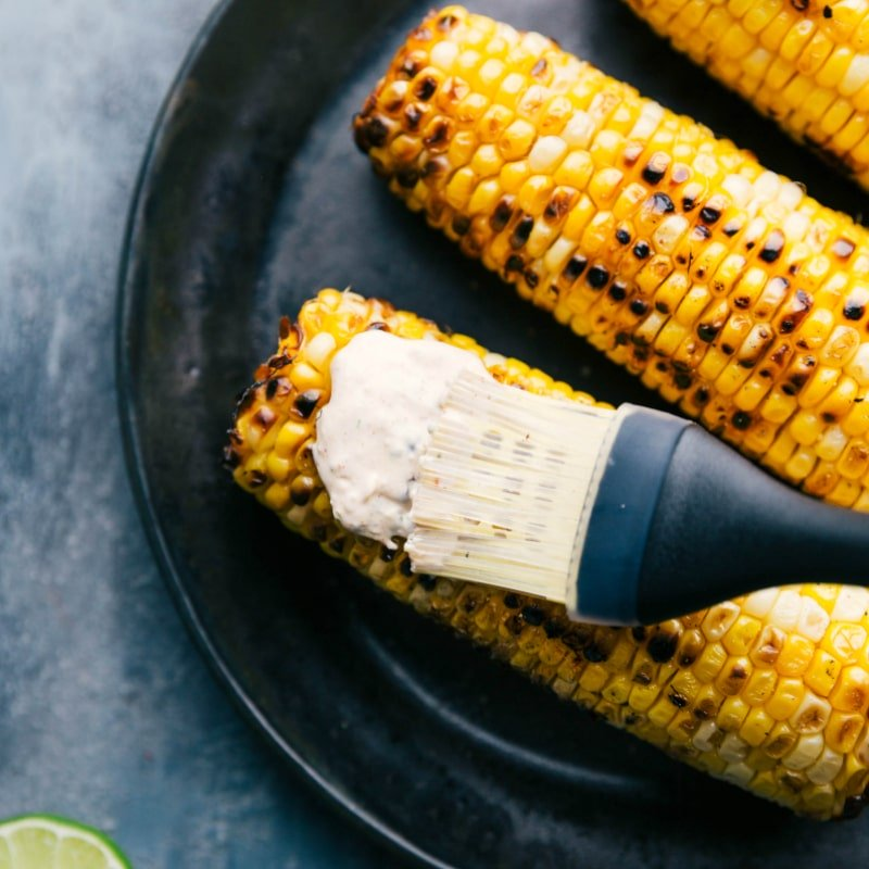 Image of the cream sauce being spread on the roasted corn on the cobs for this Mexican Elote